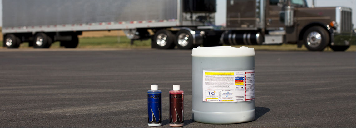 A container of Tetra-Chem and two bottles of Flash sitting on asphalt with an 18 wheeler in the background